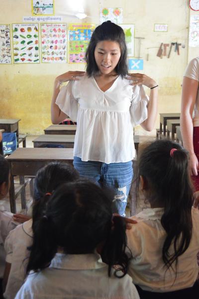 カンボジアで現地の子供たちに歌遊びを教える日本人ボランティア