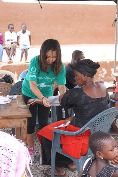 患者の血圧を測定するガーナの医療ボランティア