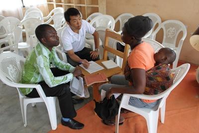 日本人マイクロファイナンスインターンが、ガーナ人女性とビジネスプランを相談している場面