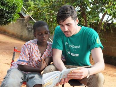 トーゴケアプロジェクト ボランティアが現地の子供に本を読んでいる様子