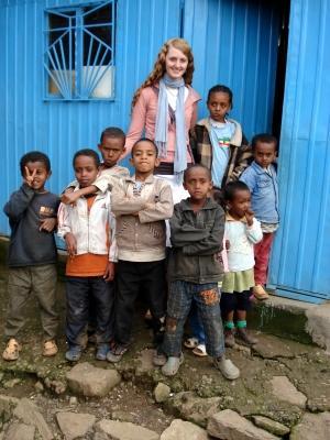 アフリカ、エチオピア、アディスアベバの学校の外にて、子供とボランティアたち