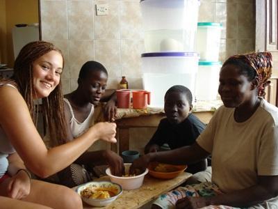 ガーナのホストファミリーと一緒に食事中のボランティア
