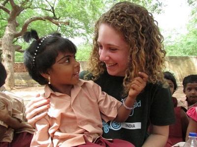 インド、活動地で子どもたちと笑うボランティア