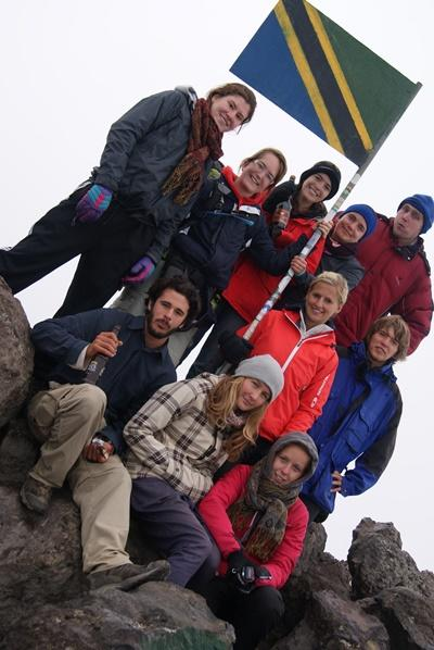 タンザニアの山頂で旗を掲げるボランティア