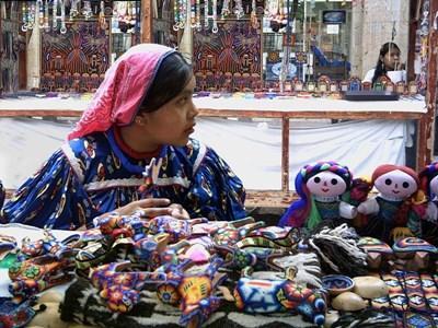 南米で手工芸品を市場で売る女性