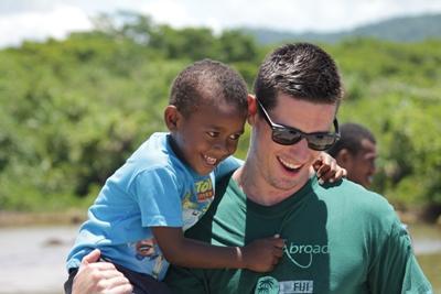南太平洋、ケアプロジェクト活動地にて男の子を抱くプロジェクトアブロードボランティア
