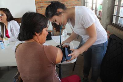 メキシコで公衆衛生プロジェクトに参加した日本人ボランティアが、血圧を測っている様子