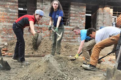 ネパールで学校再建に協力する大地震復興支援プロジェクトのボランティアたち