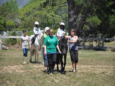 南アフリカの乗馬セラピープロジェクトで、障がいをもつ子供をサポートにあたるボランティア
