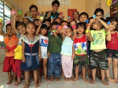 折り紙を手にポーズをとるカンボジアの子供たちと日本人ボランティア