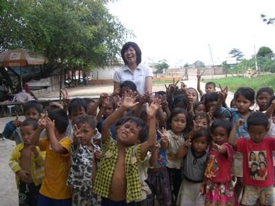 大勢の子供たちとカンボジアで働く日本人ケアボランティア