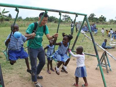 子供たちのブランコを手伝う日本人ボランティア