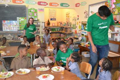 ジャマイカのケア施設で食事の時間を補助するボランティアたち