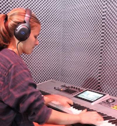 音楽制作プロジェクトのインターンが、南アフリカの最新鋭のスタジオでキーボードのレコーディングを行っている場面