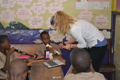 教室でジャマイカの生徒たちに楽器の使い方を教えるボランティアの様子