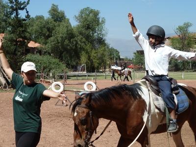 乗馬セラピーを受けるボリビアの男の子とそのサポートにあたるプロジェクトアブロードのボランティア
