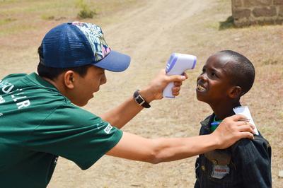 ケニアの子供の体温を測る高校生ボランティア
