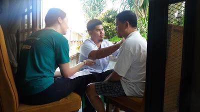 フィリピンで家庭訪問リハビリテーションに同行する高校生ボランティア