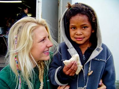 A young child in Cape Town, South Africa eats a sandwich as a Projects Abroad Intern looks on