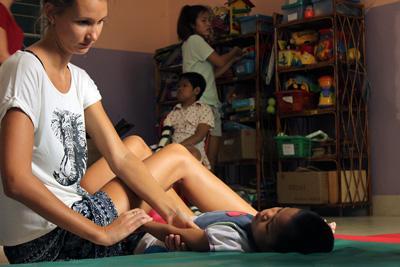 カンボジアで子供に治療を施す理学療法インターン