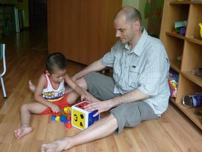 Professional Psychologist guilding child on a volunteer project in Vietnam