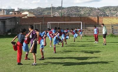 Physical education class warming up with professional volunteer in Peru
