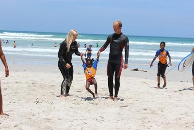 南アフリカのミューゼンバーグビーチで行われているサーフィンプロジェクトのボランティアと子供たち
