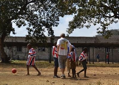 タンザニアの子供たちにサッカーを教えるボランティアの様子