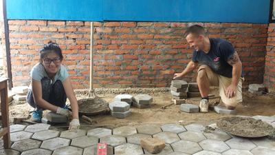 冬休みにネパールで教室の床づくりに励む建築ボランティアたち